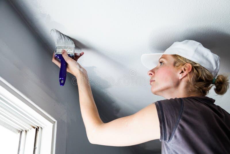 Mulher que pinta as bordas do teto imagens de stock royalty free