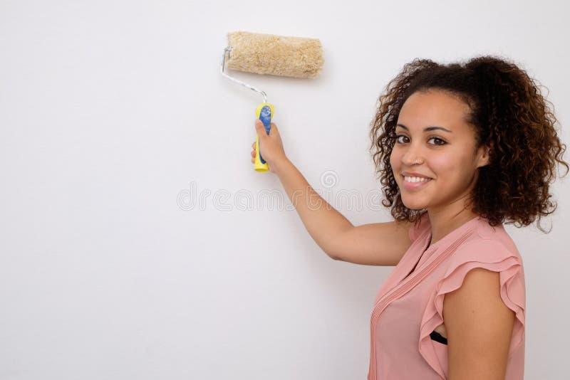 Mulher que pinta a parede de sua casa fotografia de stock royalty free