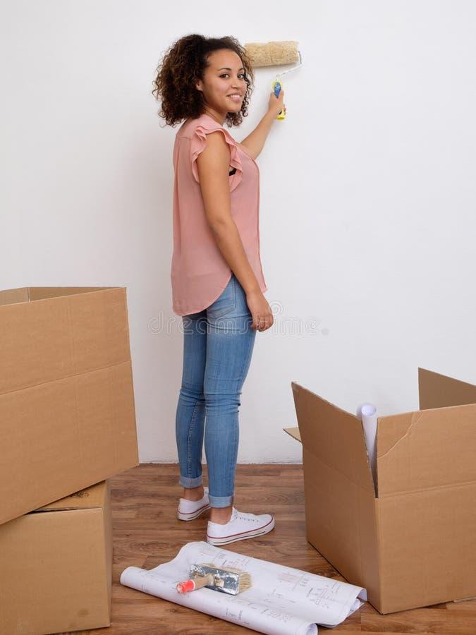 Mulher que pinta a parede de sua casa imagem de stock
