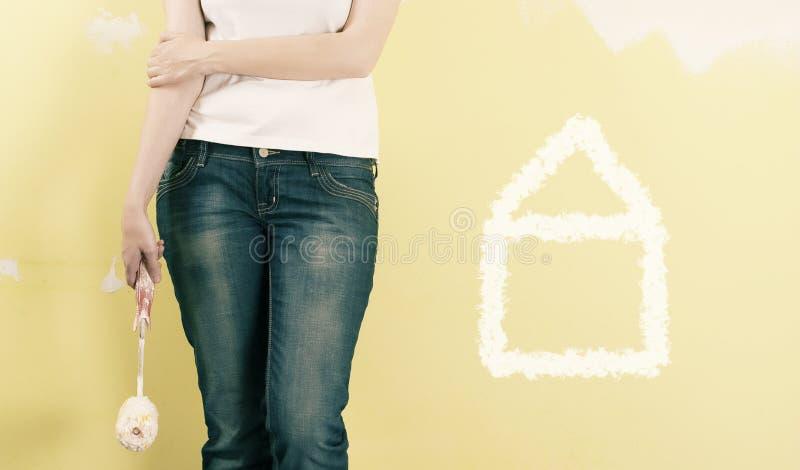 Mulher que pinta uma parede imagens de stock royalty free
