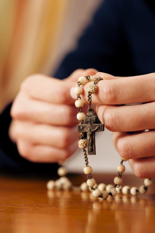 Mulher que praying com o rosário ao deus fotografia de stock royalty free