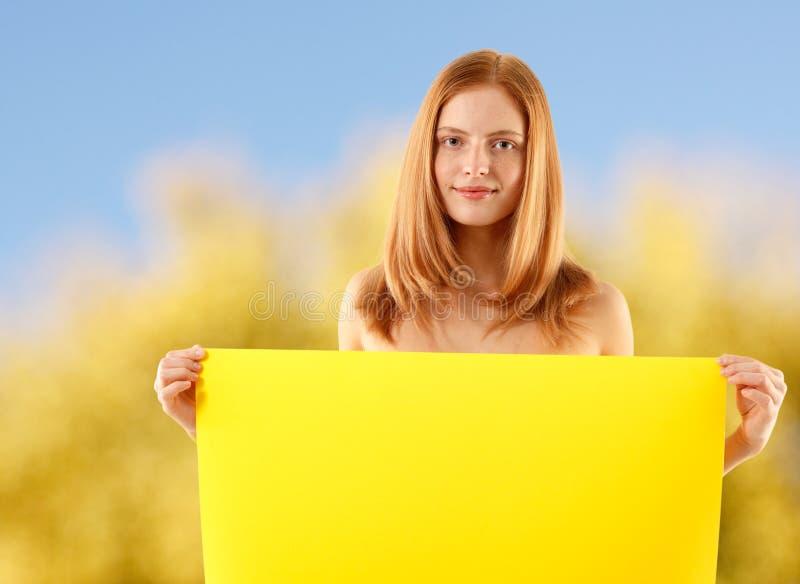 Mulher que prende a bandeira amarela em branco sobre a natureza imagem de stock