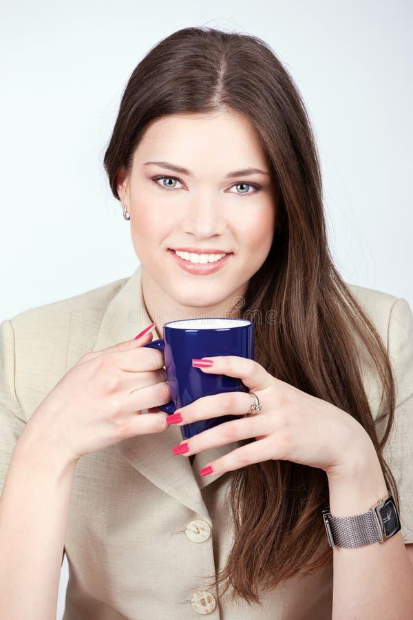 Mulher que prende a chávena de café azul imagem de stock