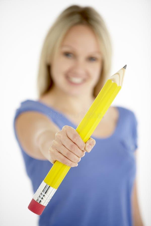 Mulher que prende o lápis grande imagens de stock
