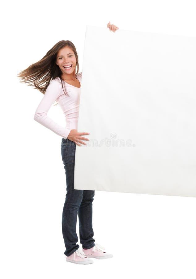 Mulher que prende o sinal em branco do quadro de avisos foto de stock royalty free