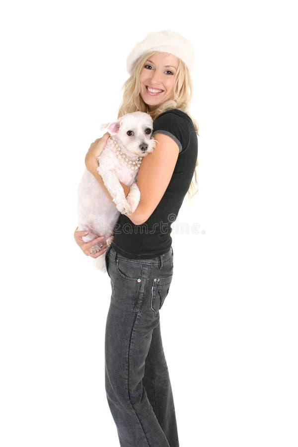 Mulher que prende um cão pequeno imagem de stock