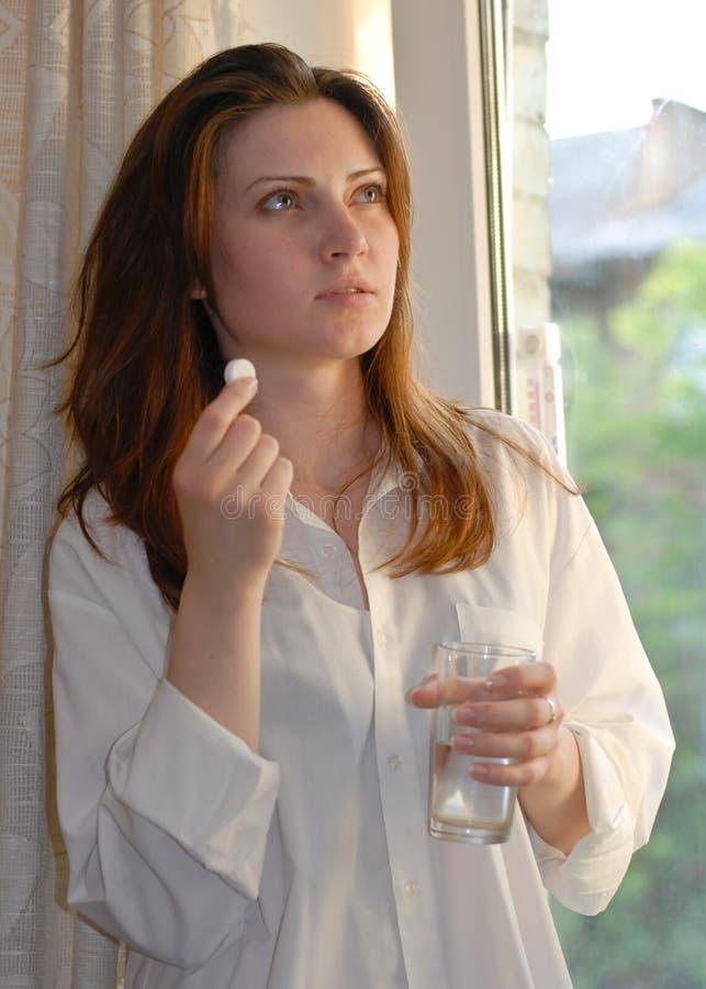 Mulher que prende um comprimido e um vidro da água fotos de stock