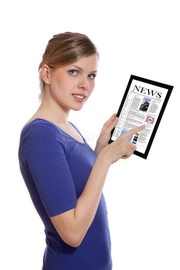 Mulher que prende um PC do touchpad, lendo um jornal foto de stock royalty free
