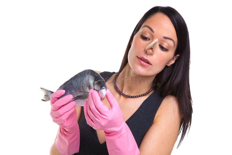 Mulher que prende um peixe cru imagens de stock