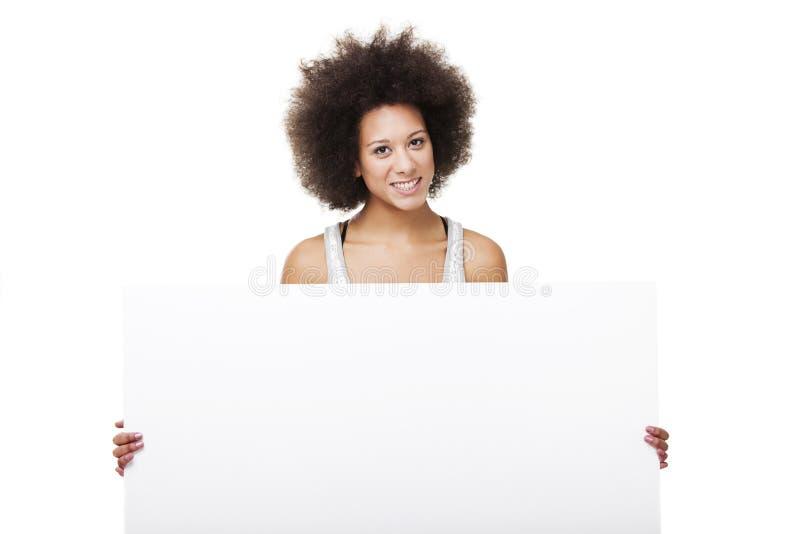 Mulher que prende um quadro de avisos branco imagem de stock
