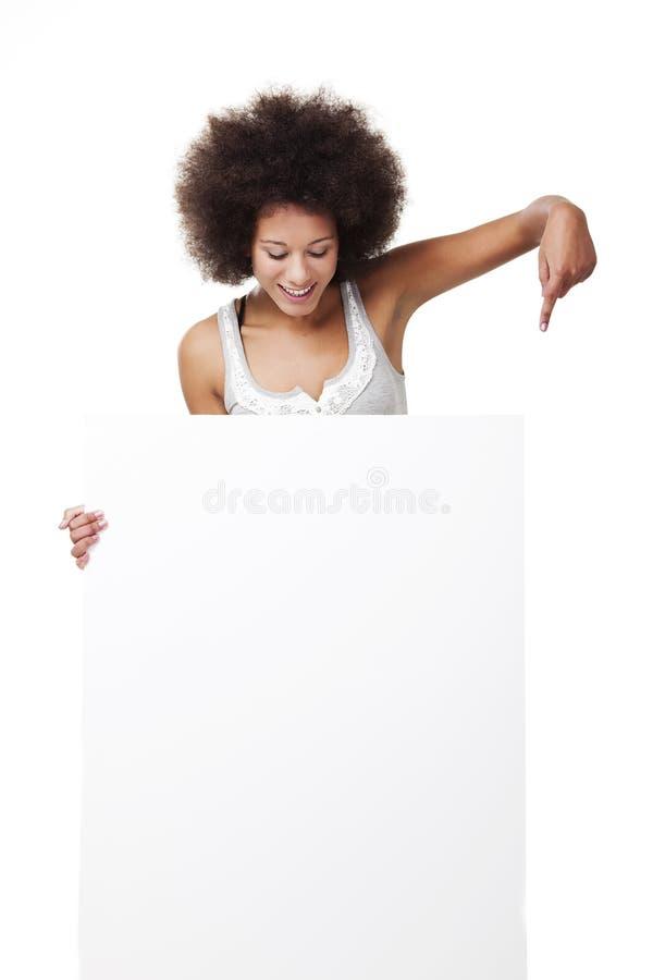 Mulher que prende um quadro de avisos branco foto de stock