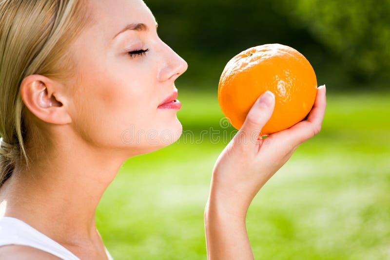 Mulher que prende uma laranja imagem de stock royalty free