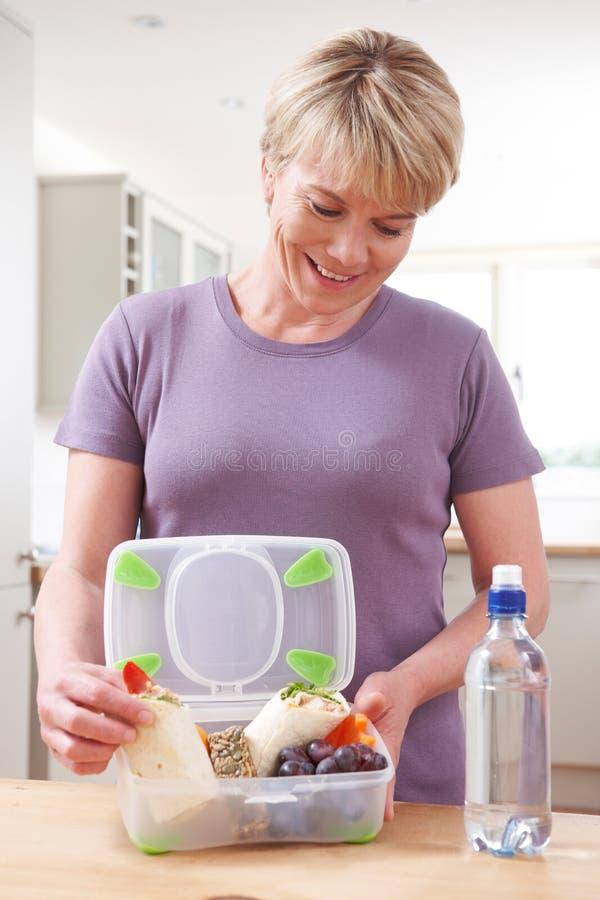 Mulher que prepara a cesta de comida saudável na cozinha foto de stock