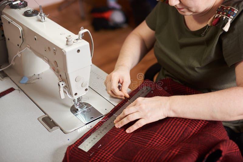 Mulher que prepara a matéria têxtil para costurar: matéria têxtil de medição da manta com régua, bordas da fixação da tela com pi imagem de stock