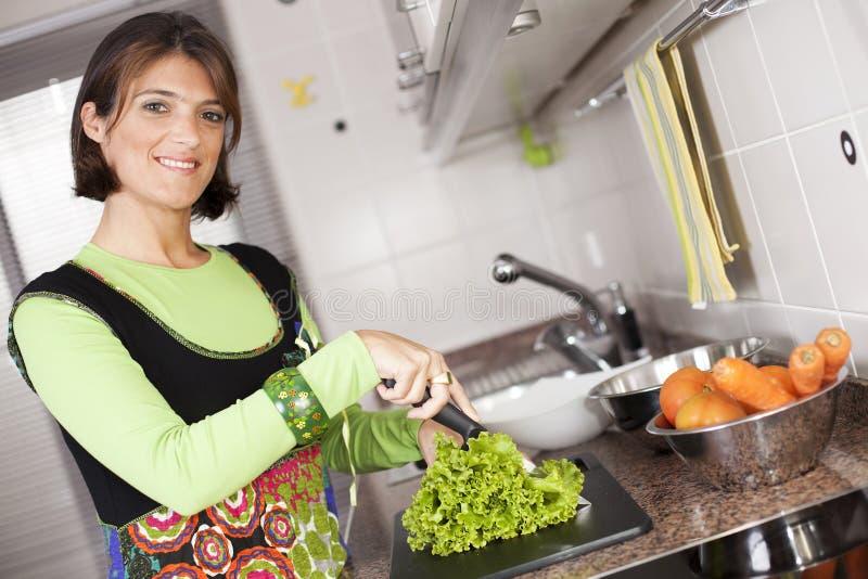 Mulher que prepara o alimento na cozinha imagem de stock