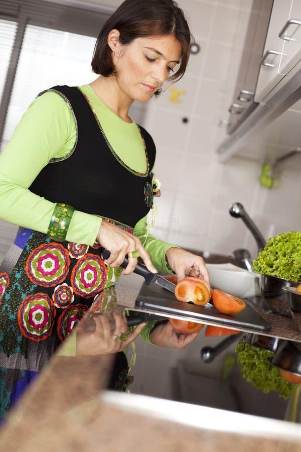 Mulher que prepara o alimento na cozinha fotografia de stock