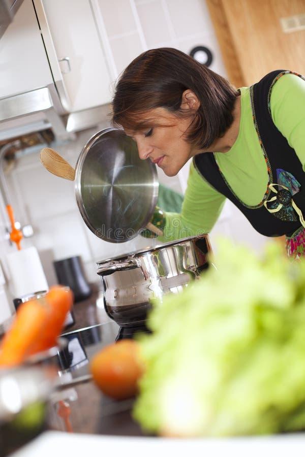 Mulher que prepara o alimento na cozinha imagem de stock royalty free