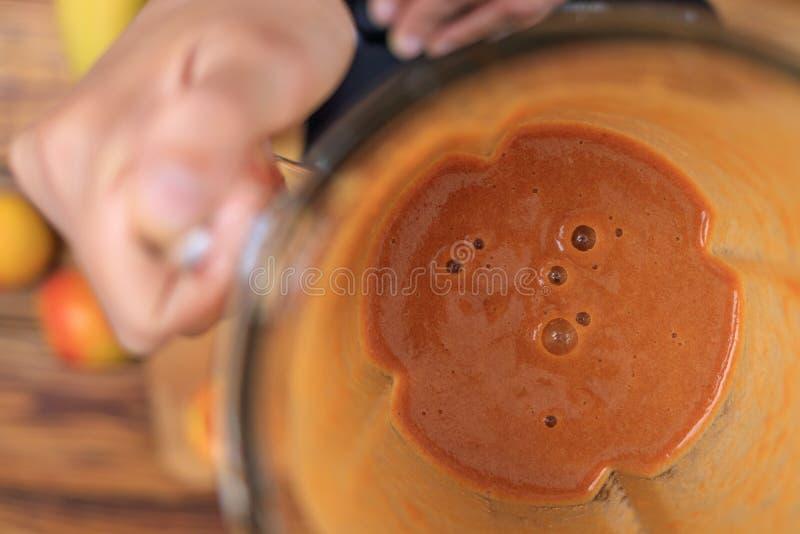 Mulher que prepara o batido ou o suco do abricó com frutos na cozinha foto de stock