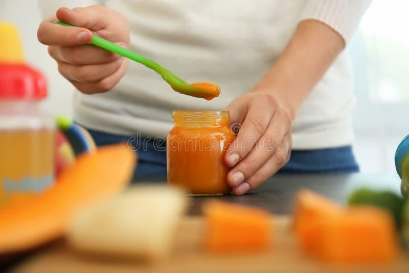 Mulher que prepara o comida para bebê saudável na cozinha, close up foto de stock