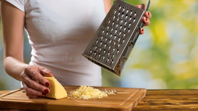 Mulher que prepara o molho para a massa e o queijo grating fotos de stock