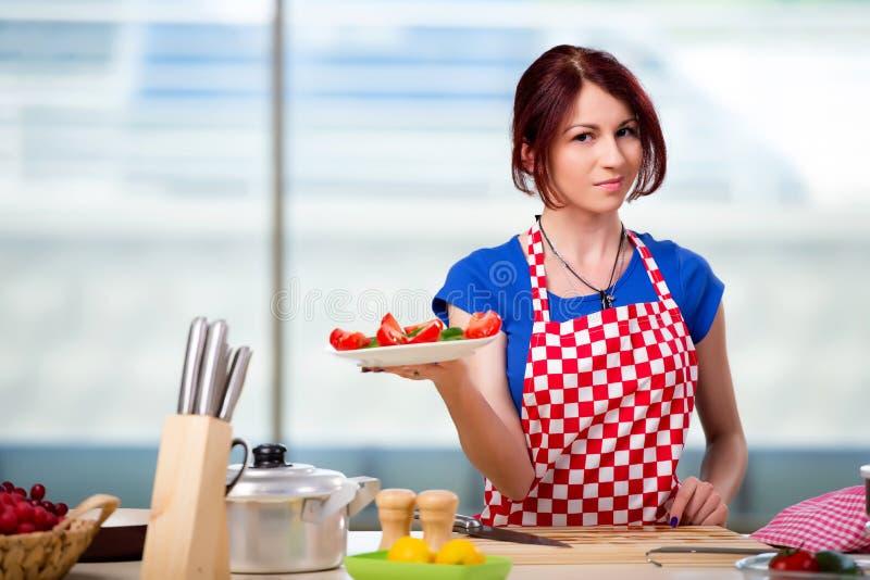 A mulher que prepara a salada na cozinha fotografia de stock