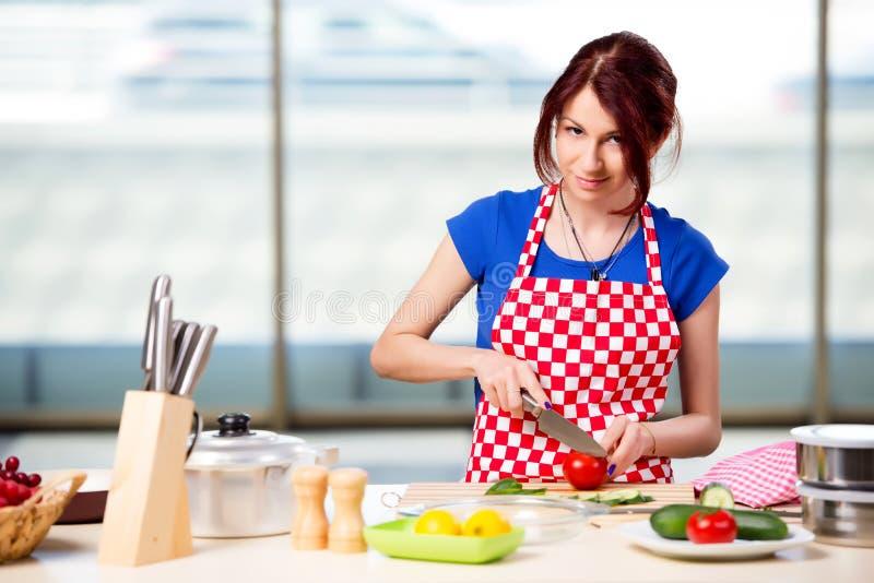 A mulher que prepara a salada na cozinha imagens de stock royalty free