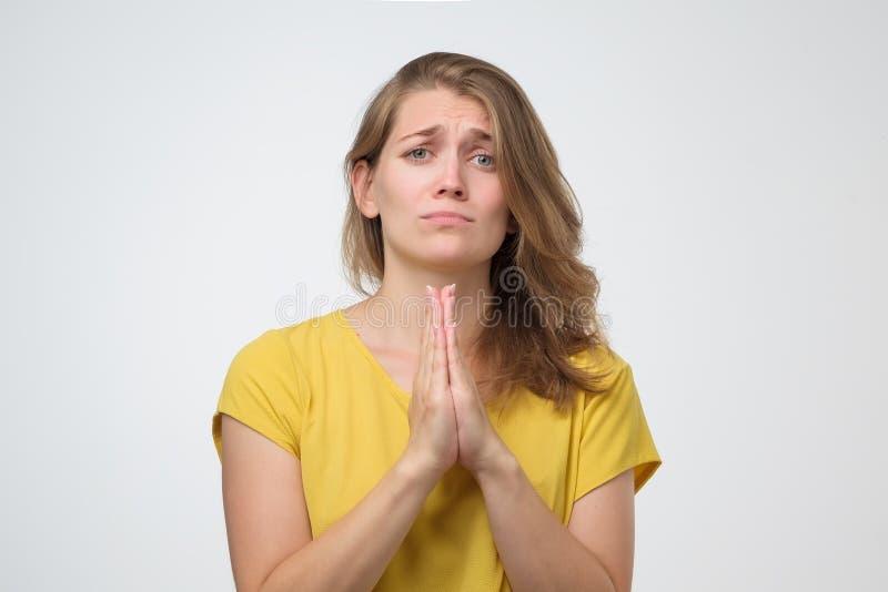 A mulher que pressiona as palmas que imploram junto reza para a ajuda imagens de stock