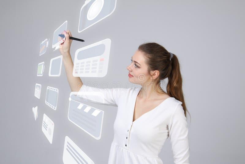 Mulher que pressiona a elevação - o tipo da tecnologia de multimédios modernos abotoa-se em um fundo virtual fotos de stock royalty free