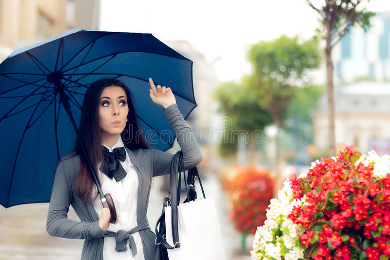 Mulher que procura um táxi no tempo chuvoso imagens de stock royalty free