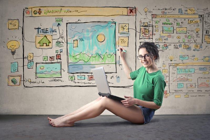 Mulher que projeta um Web site foto de stock