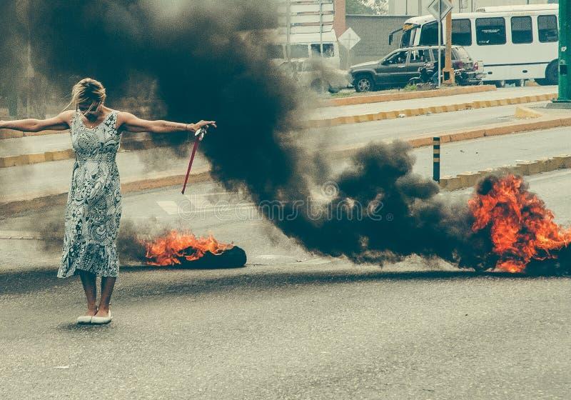 Mulher que protesta na Venezuela, pneus ardentes, fotografia de stock