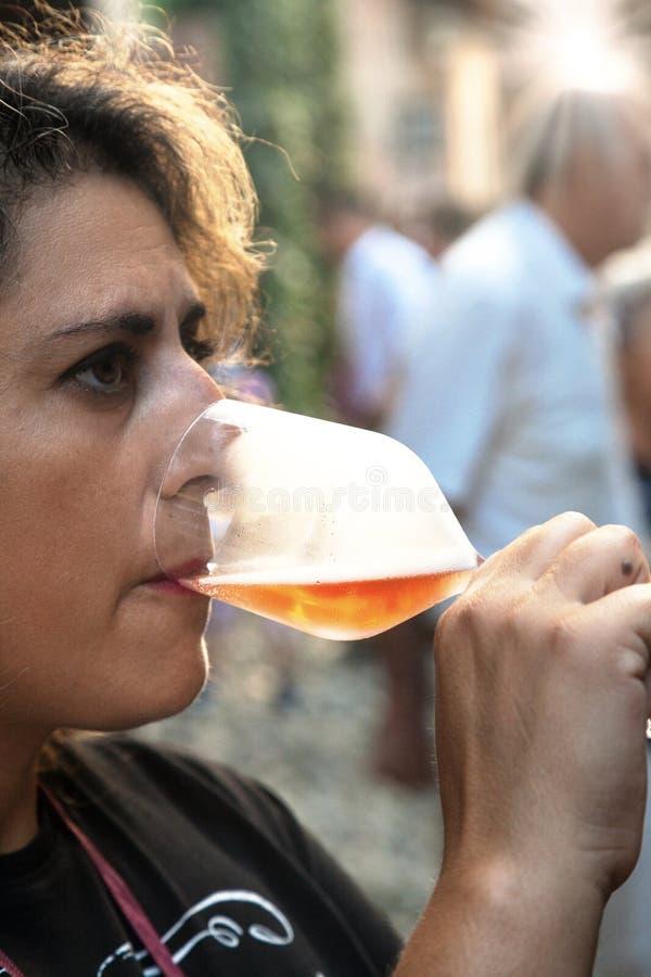 Mulher que prova um vidro do vinho branco do sparklig Imagem da cor imagens de stock royalty free