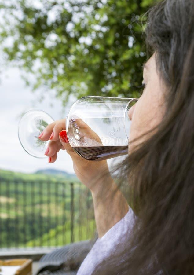 Mulher que prova um vidro do vinho vermelho Imagem da cor fotografia de stock