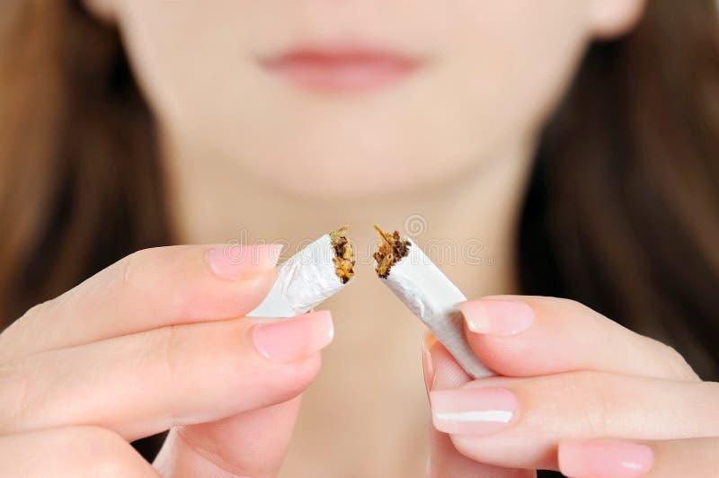 Mulher que quebra o cigarro fotografia de stock