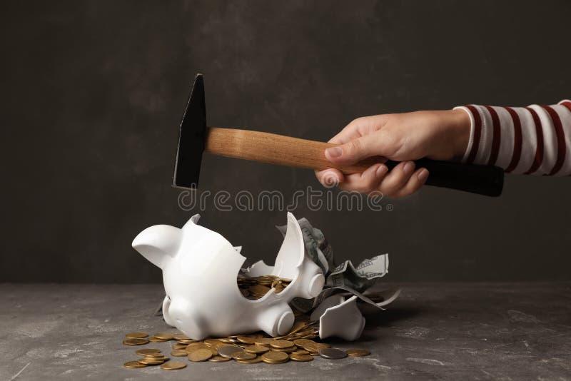 Mulher que quebra o mealheiro com martelo imagens de stock royalty free