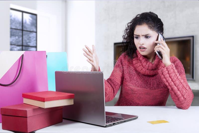 Mulher que queixa-se pelo telefone após a compra em linha imagens de stock