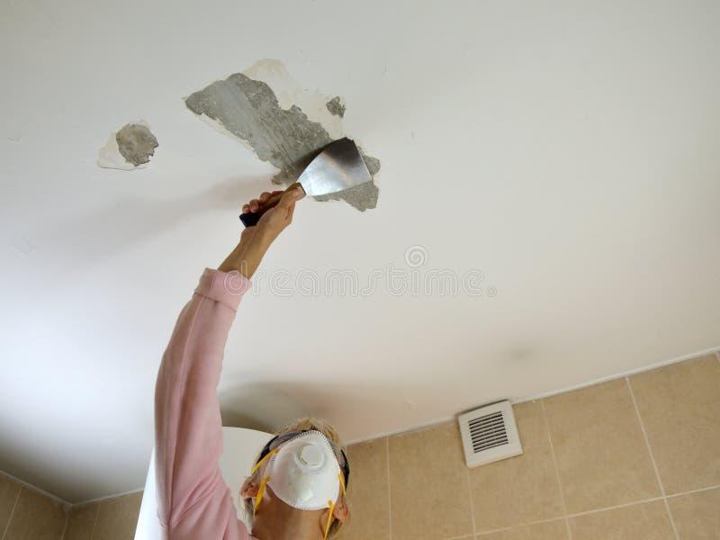 Mulher que raspa um teto foto de stock