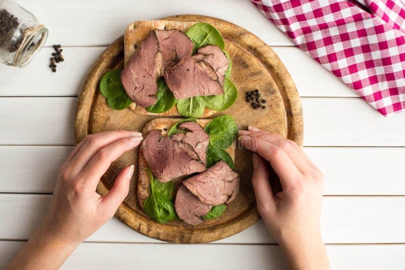 A mulher que realiza em suas mãos abre o sanduíche da carne assada com salada e pimenta na placa de madeira rústica fotos de stock