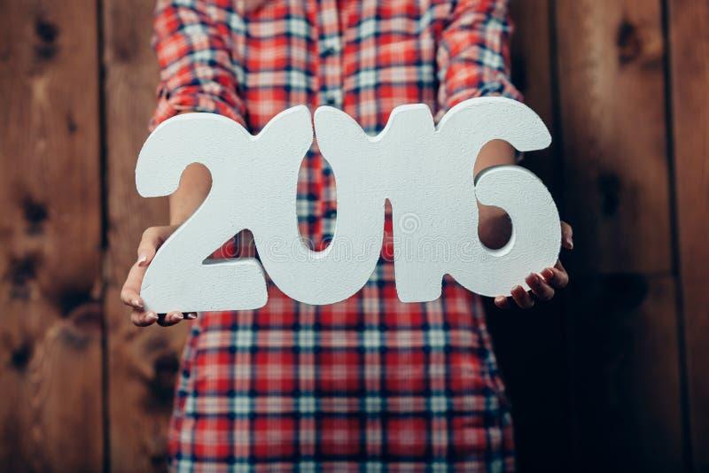A mulher que realiza no ano novo 2016 das mãos numera fotografia de stock