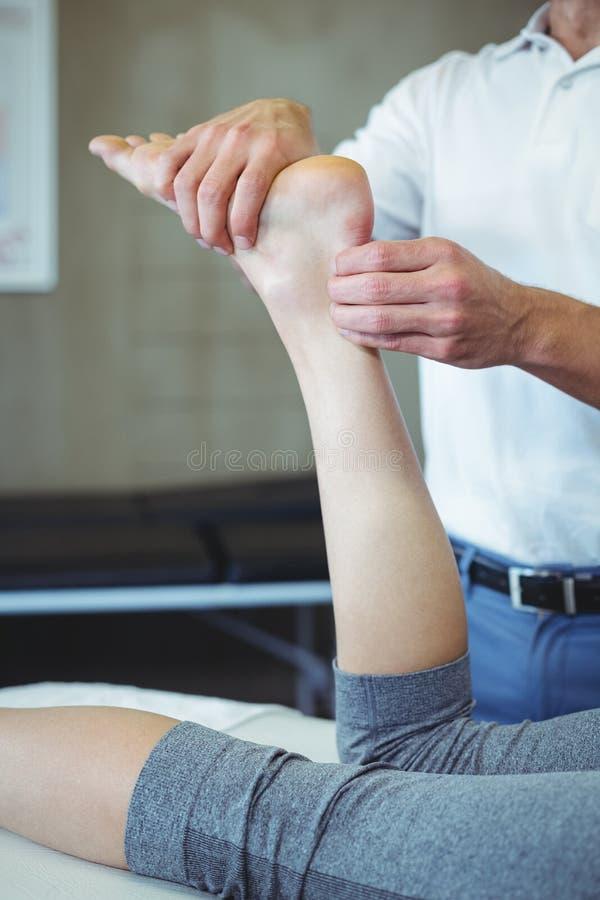 Mulher que recebe a massagem do pé do fisioterapeuta fotos de stock