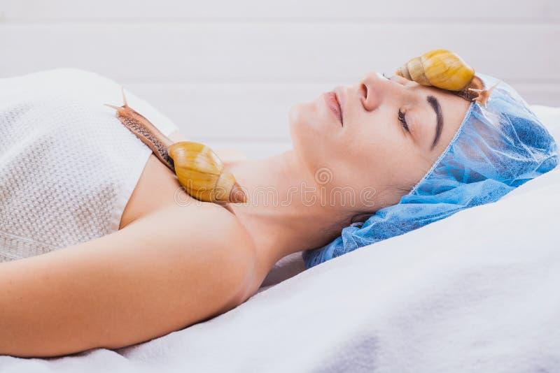 Mulher que recebe a massagem facial do caracol Caracol na cara Procedimento de limpeza no salão de beleza dos termas fotografia de stock royalty free