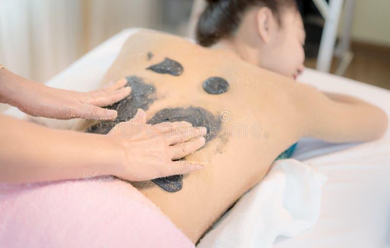 A mulher que recebe o carvão vegetal esfrega na parte traseira em termas tailandeses da massagem fotos de stock royalty free