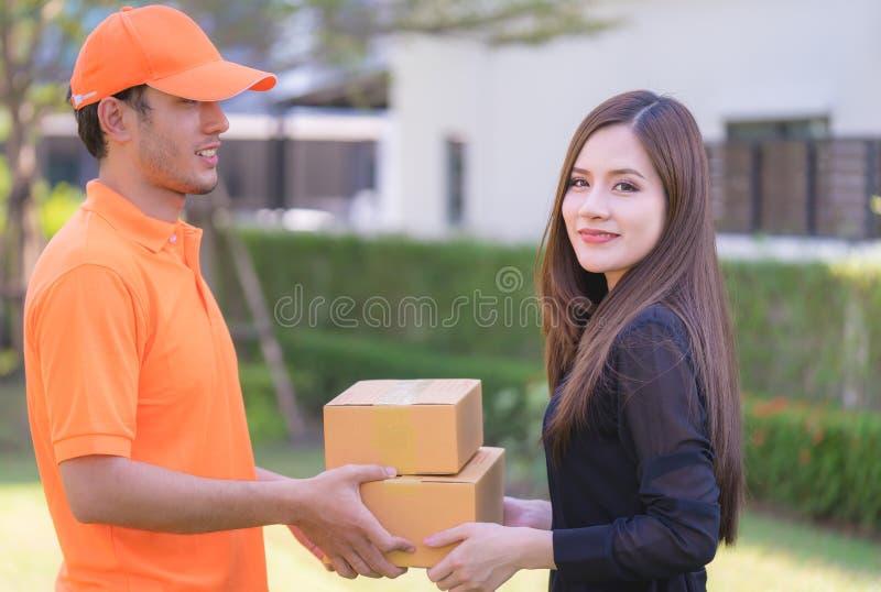 Mulher que recebe o pacote do homem de entrega fotos de stock royalty free