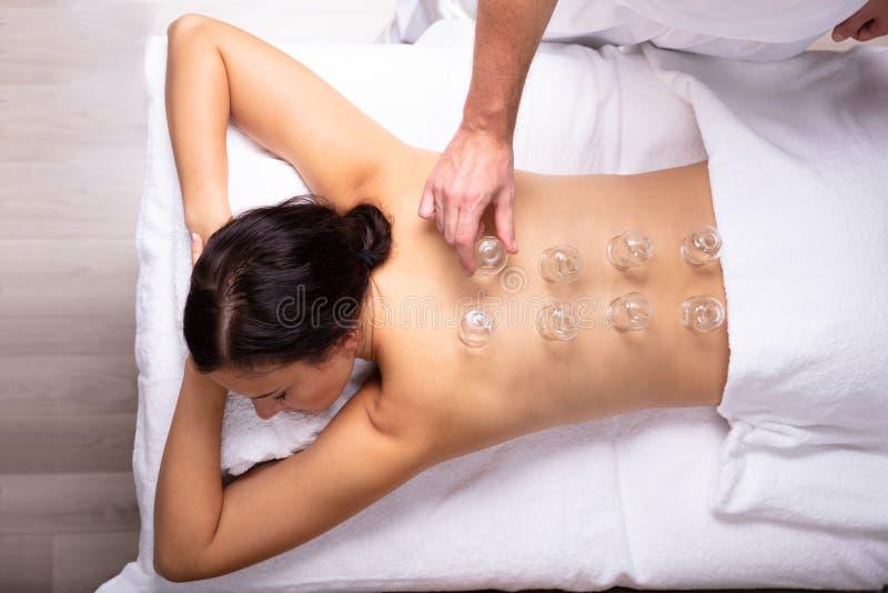 Mulher que recebe o tratamento colocando em sua parte traseira fotos de stock royalty free