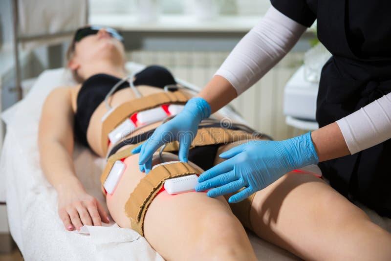 Mulher que recebe a terapia do laser do lipo do emagrecimento nos termas imagens de stock