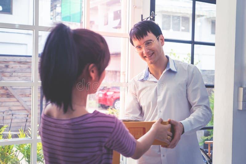 Mulher que recebe uma caixa da entrega de um homem fotos de stock royalty free