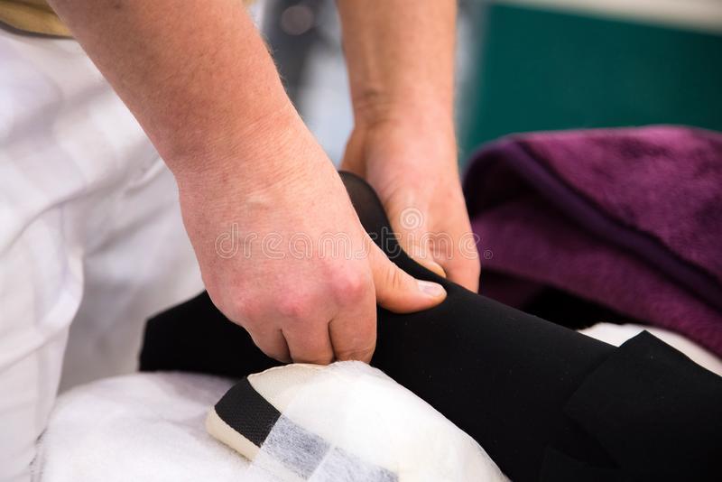 Mulher que recebe uma massagem do pé e do pé ao encontrar-se em uma toalha no centro da massagem fotos de stock royalty free