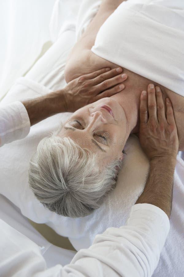 Mulher que recebe uma massagem do pescoço fotos de stock royalty free