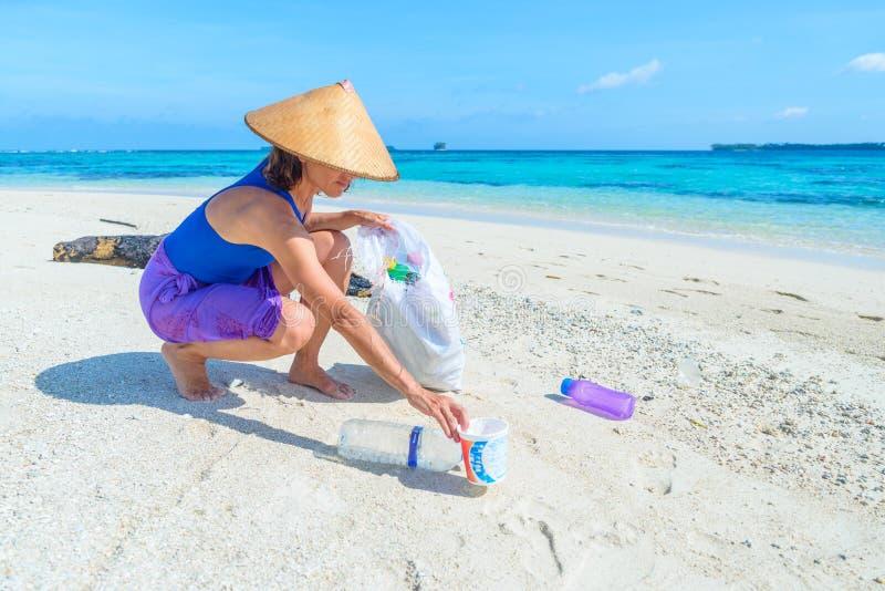 Mulher que recolhe garrafas pl?sticas na praia tropical bonita, mar de turquesa, dia ensolarado, reciclando o conceito dos desper imagens de stock royalty free