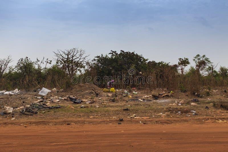 Mulher que recolhe o lixo em uma operação de descarga nos subúrbios da cidade de Bissau, em Guiné-Bissau, África ocidental imagem de stock royalty free